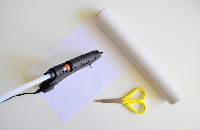 basteln aus papier, ein weißer tisch und ein weißes blatt papier und eine kleine gelbe schere, bastelanleitung, papiertüen basteln