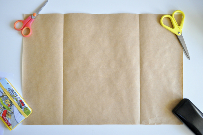 eine kleine pinke schere und ein großes braunes altes blatt papier, basteln mit papier, eine kleine gelbe schere, papiertüten basteln ohne kleben