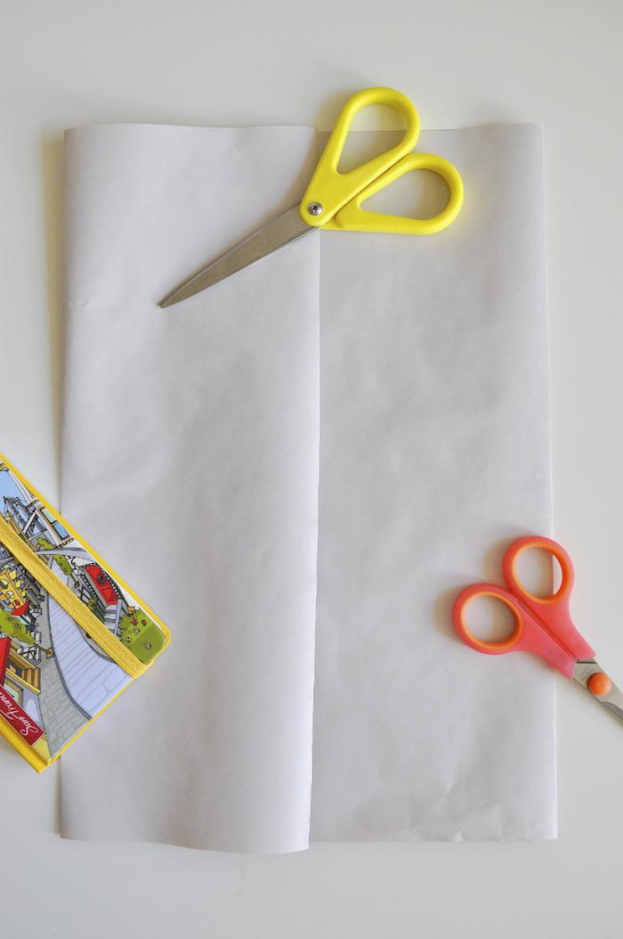 eine kleine gelbe schere und ein großes blatt papier, papiertüten falten anleitung, eeine kleine pinke schere, basteln mit kindern