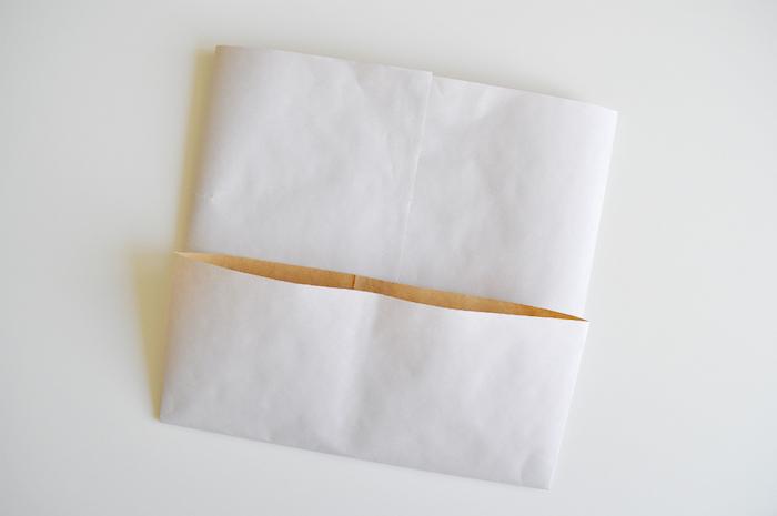 ein weißer tisch und ein gefaltetes kleknes weißes blatt papier, basteln mit papier, eine weiße papiertüte selbst basteln