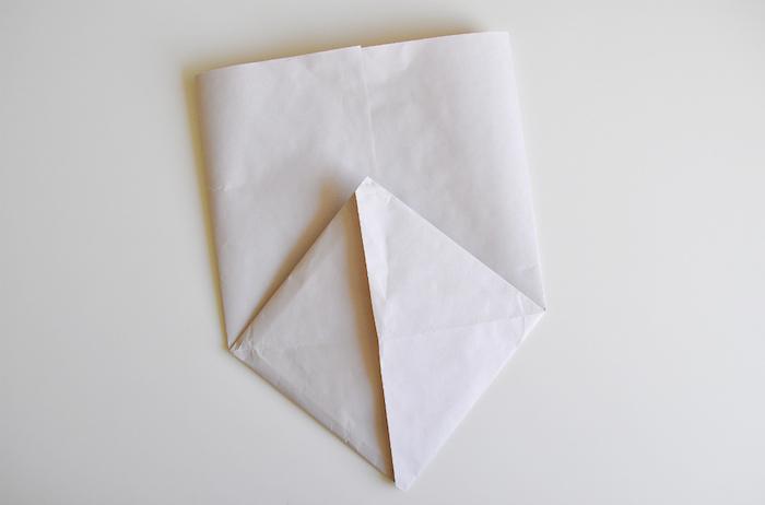 eine kleine weiße gefaltete tüte aus papier, basteln mit papier, ein weißer tisch und eine gefaltete papiertüte
