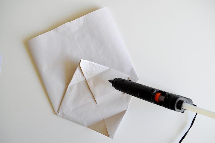 kleber und eine kleine weoße gefaltete tüte aus einem alten weißenblatt papier und ein weißer tisch, basteln mit papier