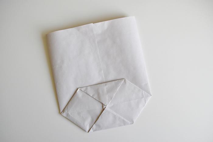 basteln mit papier, ein weißer tisch und eine kleine weiße gefaltete tüte aus einem alten weißen blatt papier, papiertüten falten anleitung