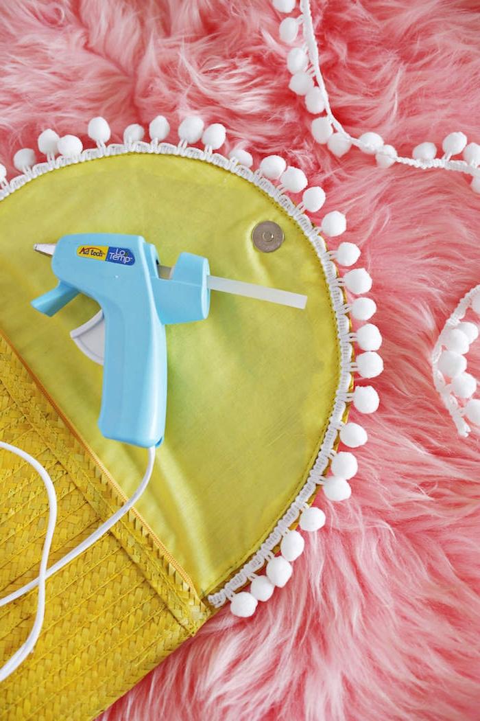 Gelbe Clutch selbst verzieren, weiße Pompons mit Heißklebepistole befestigen