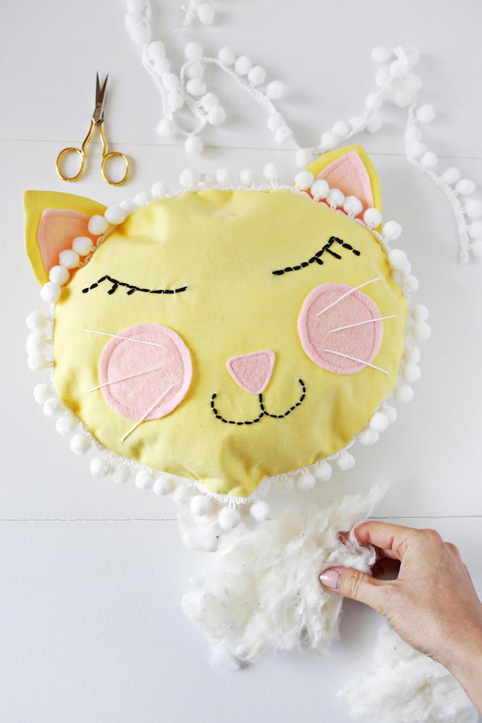 Kissen aus gelbem Stoff mit Watte füllen, Ohren und Wangen aus rosa Stoff, mit weißen Pompons verziert
