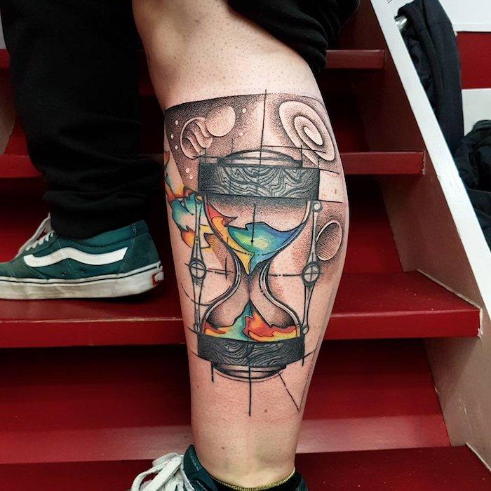 bild mit roten treppen, zwei beine mit grünen schuhen, ein bein mit einem großen sanduhr tattoo, eine schwarze sanduhr mit bunten bergen und wasser, tattoo mit kleinen planeten und sternen