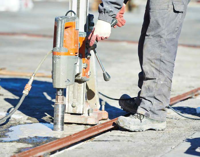 kernbohrung, maschine zum bohren von löchern in beton, mann mit kernbohrer, beton bohren