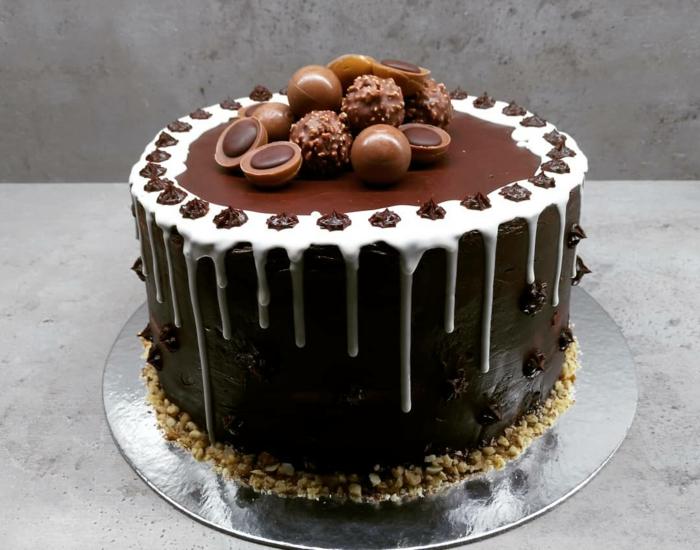 eine Torte mit Schokolade Glasur, drei Arte von Praline als Dekoration, Toffifee Torte