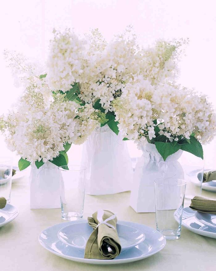 Serviette Kommunion in einem Teller, drei Vasen voller weiße Blumen