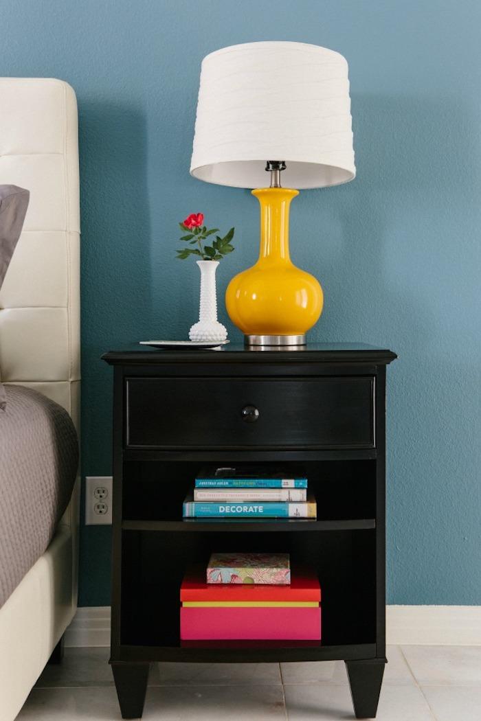 schlafzimmer Einrichtung, Wandfarbe Himmelblau, schwarzer Nachttisch aus Holz, Nachttischlampe mit weißem Schirm, kleine Vase, rote Rose