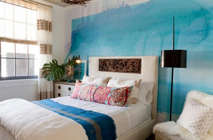 Wohnzimmer Einrichtung, Wandfarbe Blau, weißes Bett, schwarze Stehlampe, Kissen mit Blumenmuster