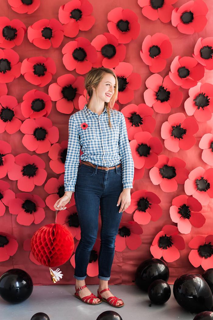 Viele rote Blüten aus Papier an der Wand, schwarze Ballons auf dem Boden, Frau mit dunkelblauen Jeans und kariertem Hemd