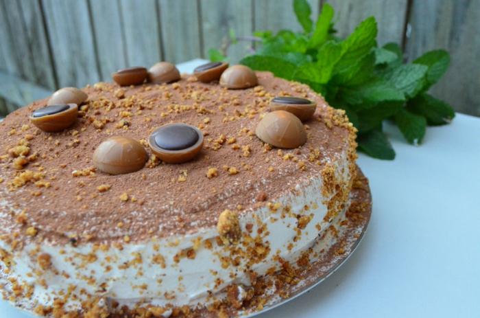 eine Torte mit weißer Creme und Toffifee Pralinen als Dekoration, mit Zimt bestreut, Toffifee Torte