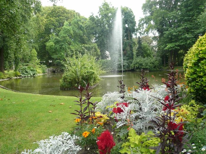 ein Wasserspiel im Garten, der selber zu machen ist, viele farbenfrohe Blumen, ein gepflegter Rasen