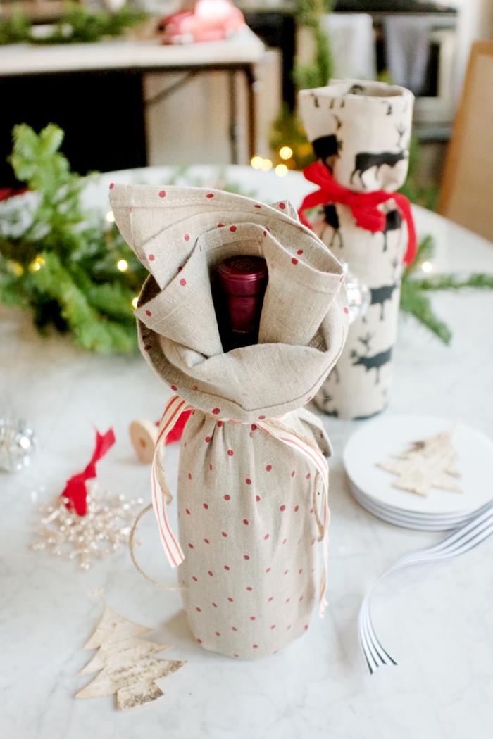 Flasche als Geschenk verpacken, graues Tuch auf kleine rote Flecken, Geschenk zu Weihnachten