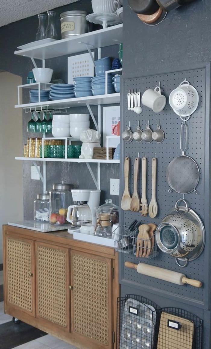 Wandgestaltung Küche mit gehängtem Küchenzubehör, Geschirr auf Regalen, blaue Wand