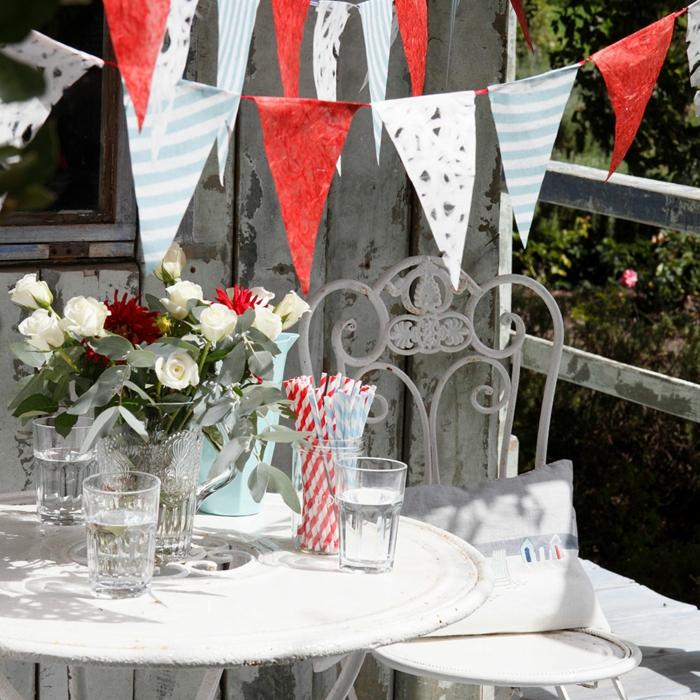 kleine flaggen in dreieck form, Gartenparty Deko ideen einfach, rote und weiße rosen, bunte strohhalme, gläser