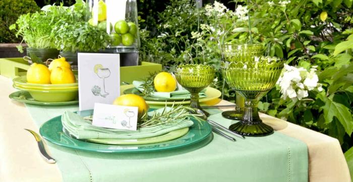 bunte partyartikel in grün und gelb, große glasgeschirrstücke, zitronen, frisches obst als deko