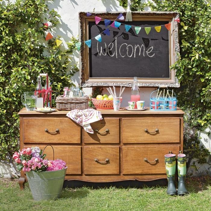 party deko zum willkommen, schwarze tafel mit aufschrift welcome, schrank als hilfstisch im garten
