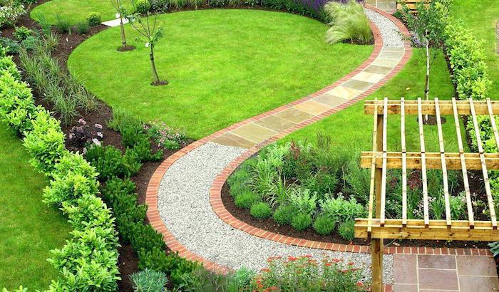 deko ideen garten, pfad mit naturstein, grüner gras, kleine büsche, gartendeko