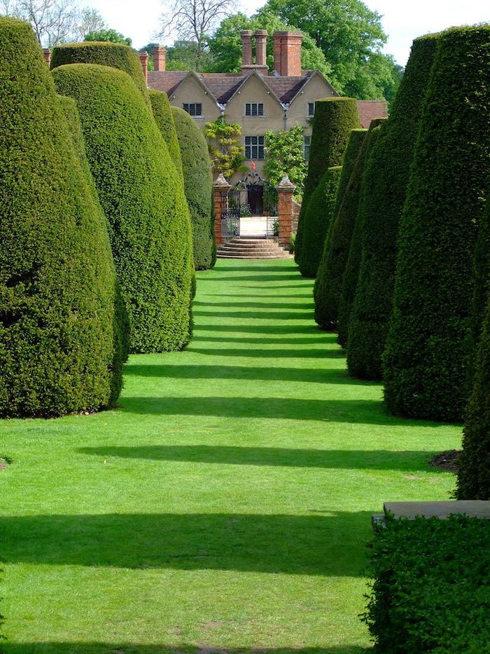 deko ideen garten, große grüne büsche, tunnel, gras, haus mit mittelalterlischem stil