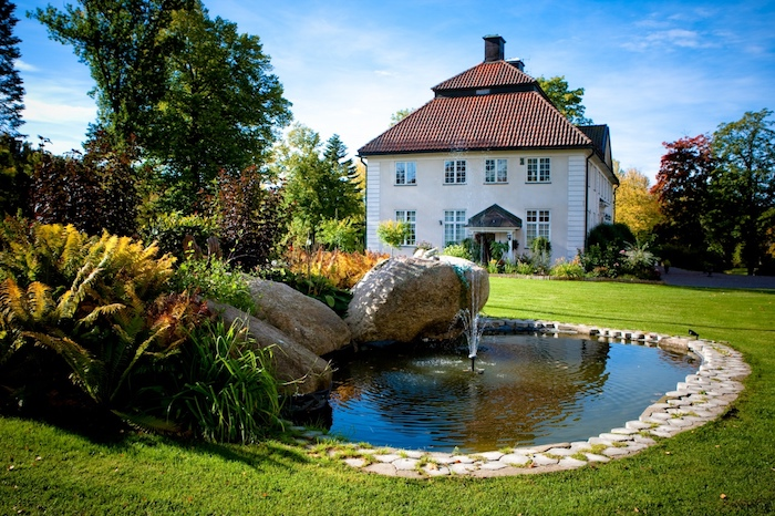 deko ideen garten, haus im landhaus stil, große steine, kleiner künstlicher see mit fontäne
