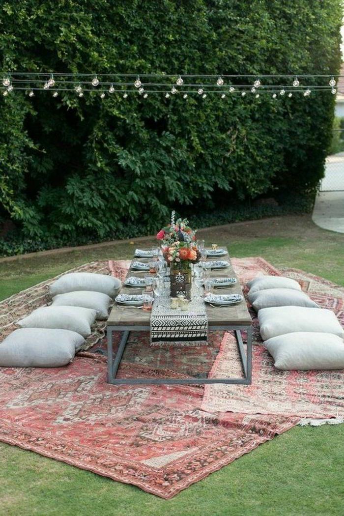 geburtstagstischdeko idee im exotischen orientalischen stil, einfache deko im garten, ein bunter teppich, viele bodenkissen, paletttisch, leuchte und blumen