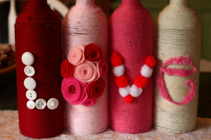 vier Flaschen, die die Aufschrift Liebe formen, Flaschen als Geschenk verpacken