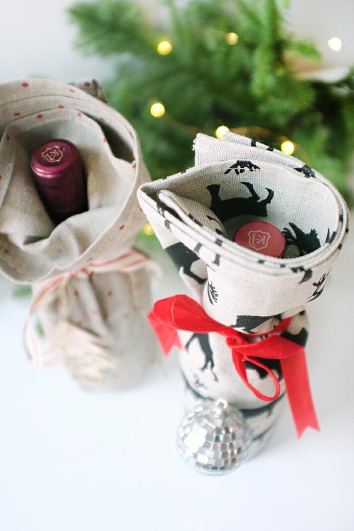 zwei verpackte Flaschen mit grauen Tüchern, Flasche als Geschenk verpacken zu Weihnachten