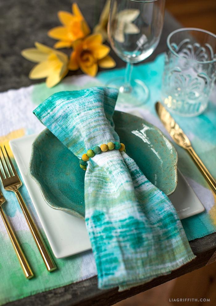 eine tischdekoration selber machen, ein kleiner grüner teller, eine gefaltete grüne serviette, ein goldenes messer und eine gelbe goldene gabel, drei gelbe blumen und gläser