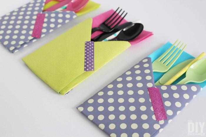ein weißer tisch, bestecktaschen falten, drei violette und gelbe bestecktaschen mit violetten, grünen und schwarzen messern, löffeln und gabeln
