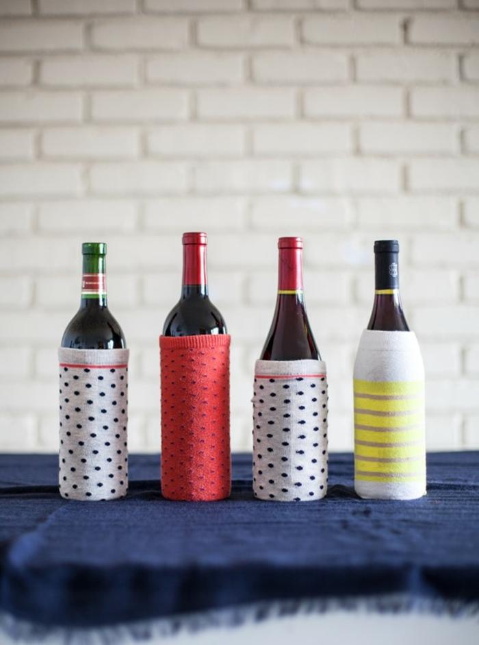 vier Flaschen, zwei graue, eine rote und eine gelbe, Flasche als Geschenk verpacken
