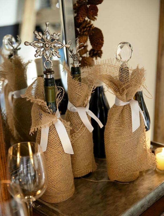 Flascheverpackung aus Sackleinen, weiße Schleifen, ornamente auf den Korken