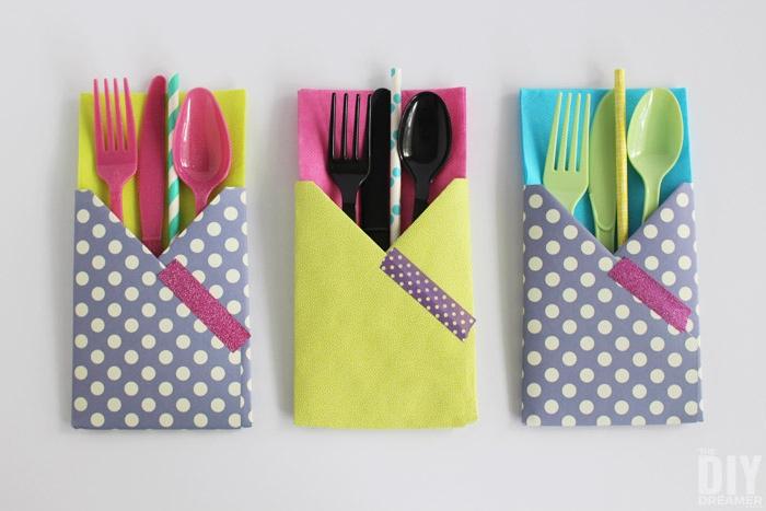 ein weißer tisch, servietten falten einfach und wirkungsvoll, drei bestecktaschen mit violetten, schwarzen und grünen löffeln, messern und gabeln und mit strohhalmen