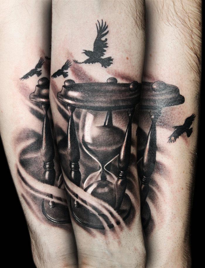 vier kleine schwarze fliegende vögel mit schwarzen federn, eine große schwarze sanduhr aus holz und mit einem schwarzen sand, sanduhr tattoo