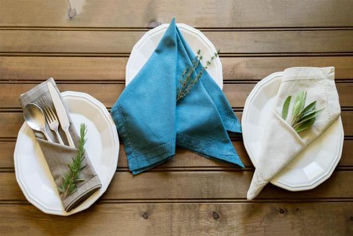 ein tisch aus holz, drei weiße teller mit grauen, blauen und weißen gefalteten servietten mit grünen pflanzen, eine graue bestecktasche mit einem löffel, einem messer und einer gabel