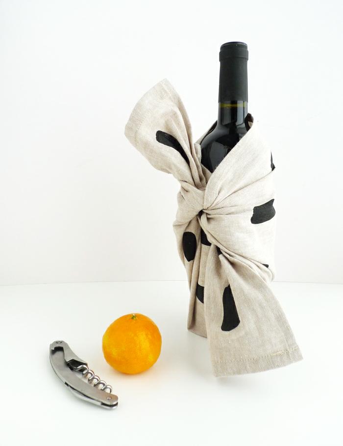 ein Korkenzieher, eine Orange und eine verpackte Weinflasche, Flasche verpacken