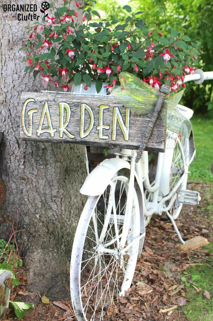 ein Aufschrift Garten auf hölzerner Tabelle, ein alter Fahrrad in weißer Farbe gestrichen, Garten gestalten mit wenig Geld