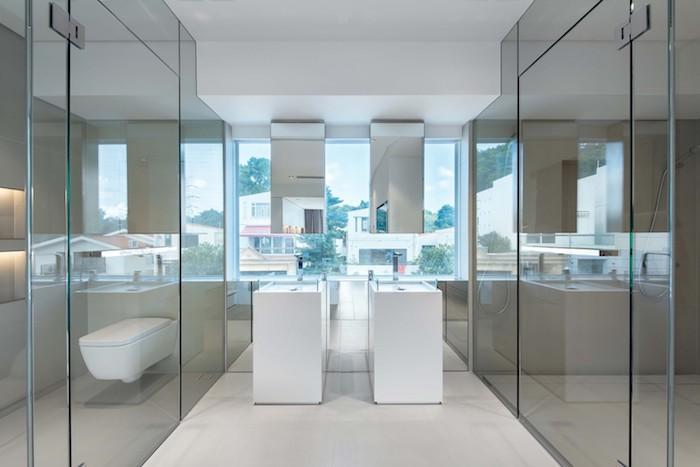 ein großes weißes waschbecken und zwei spiegel, ein fenster und zwei häuser und große grüne bäume, ein badezimmer einrichten