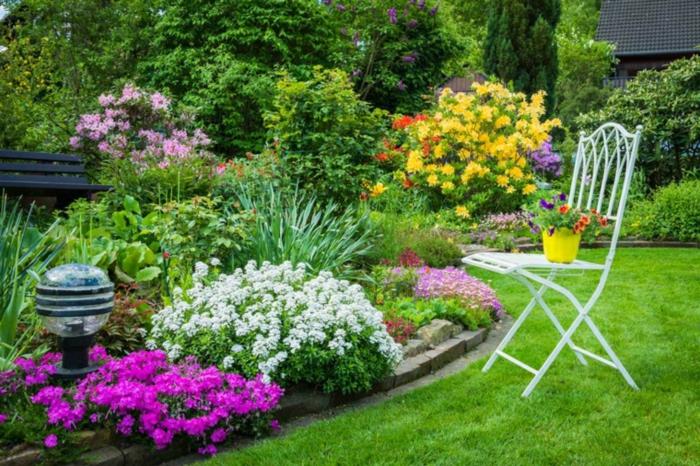 bunte Beete, ein weißer Stuhl als Dekoration, gepflegter Rasen, Garten gestalten mit wenig Geld