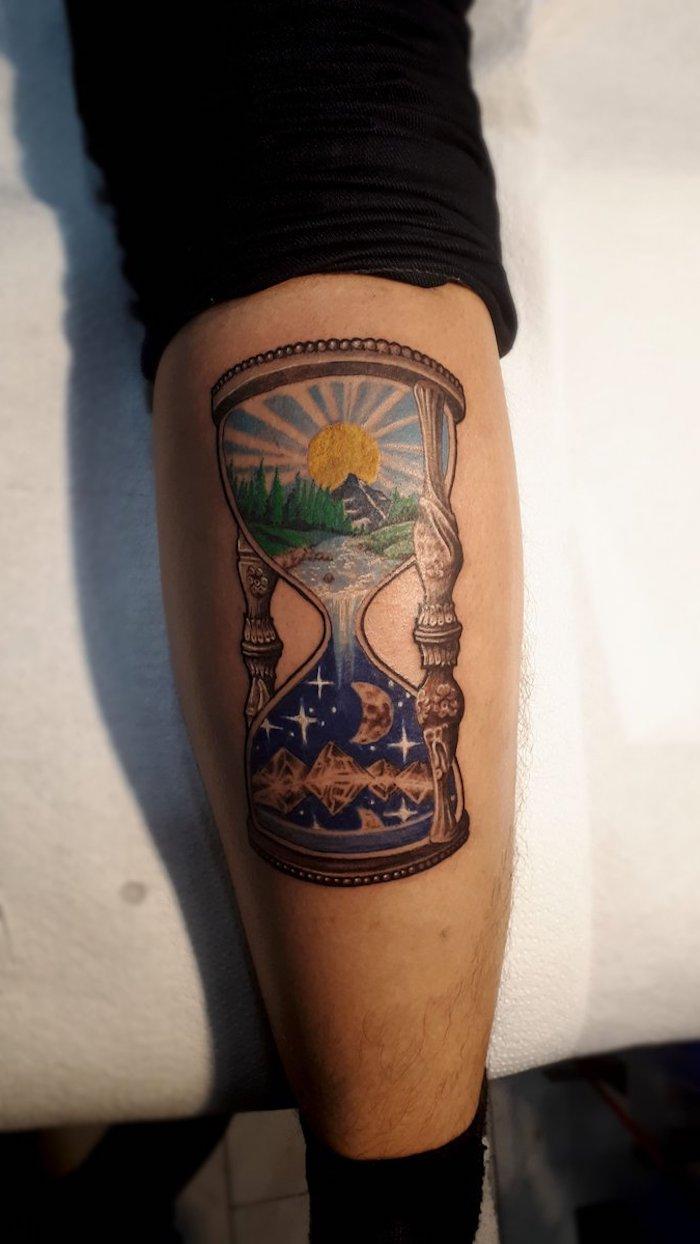 große graue sanduhr mit einem blauen himmel mit vielen kleinen weißen sternen und mit einem mond und einer gelben sonne, grünen bäumen, wäldern und gluss, ein sanduhr tattoo