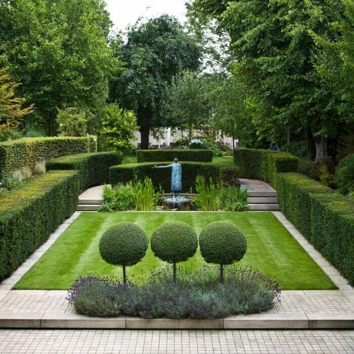 geometrisch geformte Hecke, eine Menschenfigur, viele hohe Bäume, Garten gestalten mit wenig Geld