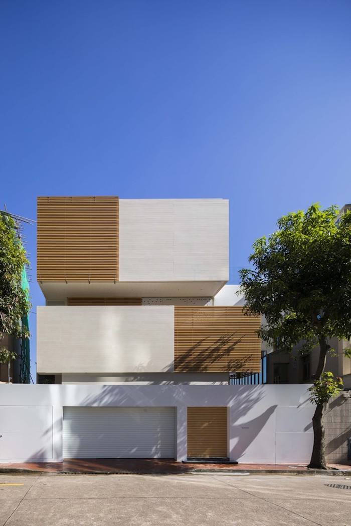 ein dreistöckiges weißes großes haus mit garage und mit wänden aus holz, große bäume mit vielen grünen blättern, haus einrichtung