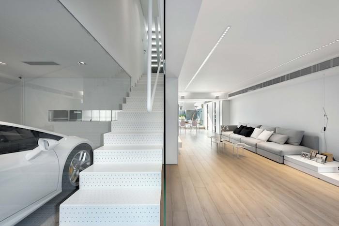 ein großes wohnzimmer mit grauen sofas mit scwarzen, weißen und grauen kissen, einem kleinen weißen tisch aus holz, wohnzimmer einrichten, weiße treppen und ein großer weißer wagen