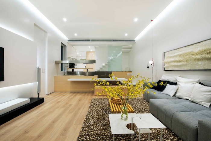 ein kleiner weißer tisch mit einer vase mit vieleb gelben blumen, ein haus einrichten, graue sofas mit schwarzen und weißen kissen, ein waschbecken und eine weiße treppe und ein boden aus holz