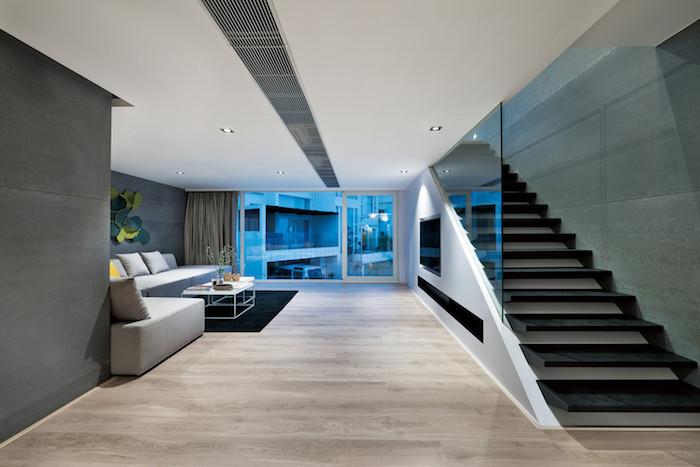 eine große schwarze lange treppe und ein bolden aus holz, ein haus einrichten, ein wohnzimmer mkt grauen wänden und mit grauen sofas mit grauen und orangen kissen und ein kleiner weißen tisch, zimmer einrichten ideen