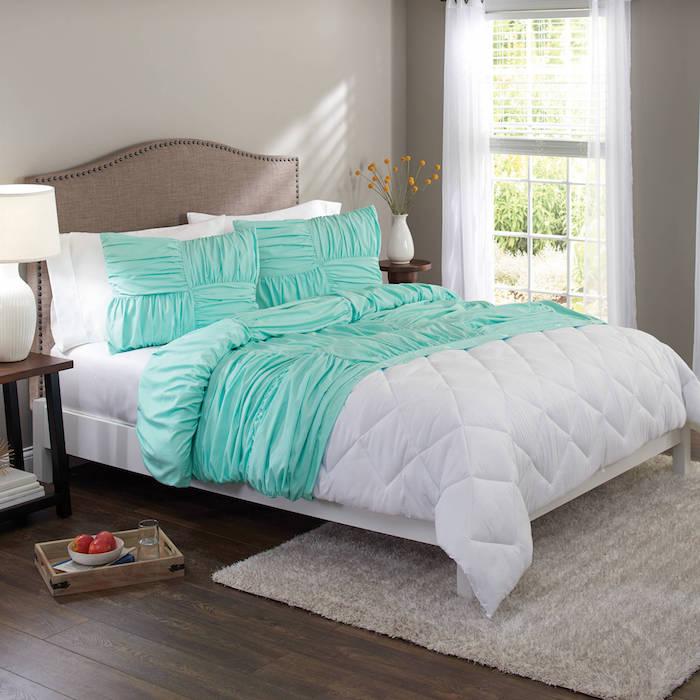 ein großes bett mit grünen und weißen kissen, ein kleiner brauner tisch aus holz und mit einer kleinen weißen lampe, eine weiße vase mit orangen blumen, schlafzimmer einrichtung