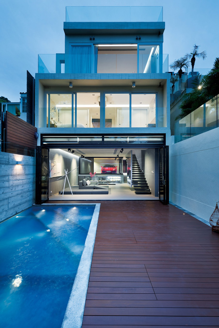 ein pool und ein dreistöckiges haus mit fenstern und mit einem wohnzimmer mit schwarzen treppen und mit einem roten wagen u, grauen sofas und grauen wänden, haus einrichten