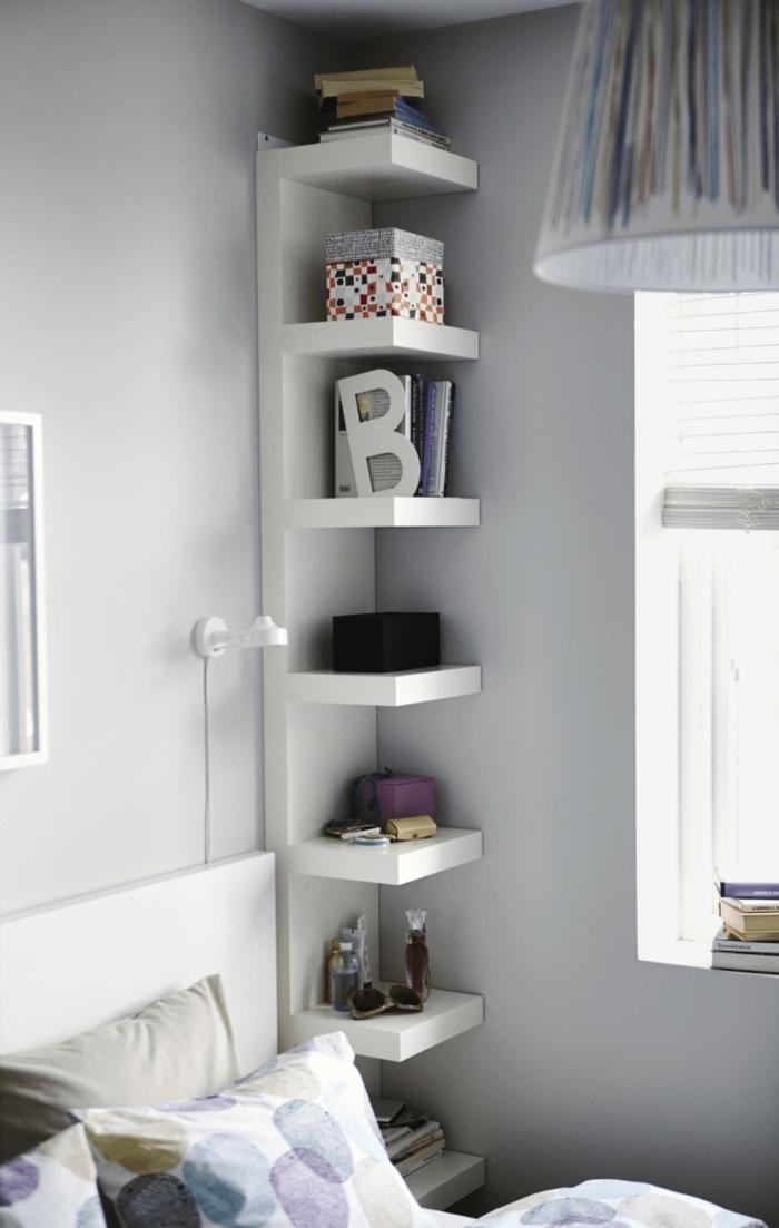 ein Regal in der Ecke mit vielen Büchern, weiße Wände, bunter Lampenschirm, kleine Räume einrichten