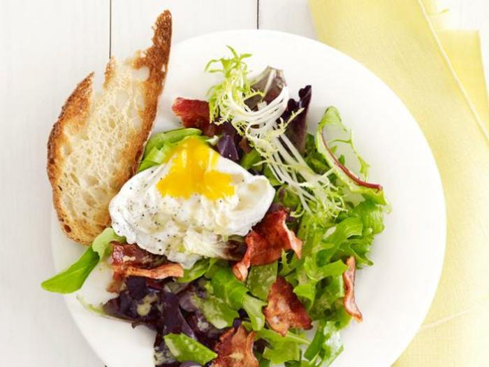 grüne Blätter, Rucola, ein Spiegelei, Stück Brot, gesunde Salate